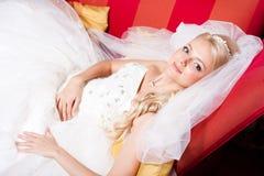 Mooie bruid die op rode bank ligt Royalty-vrije Stock Fotografie