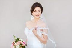 Mooie bruid die tegen een grijze muur glimlachen royalty-vrije stock fotografie