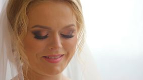 Mooie bruid die uit venster kijken en op haar huwelijksdag glimlachen stock footage
