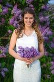 Mooie bruid die zich met bloemen dichtbij bloeiende lilac boom bevinden Stock Fotografie