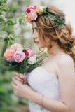 Mooie bruid in een huwelijkskleding met boeket en van de rozenkroon het stellen in een groene tuin Royalty-vrije Stock Foto
