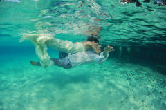 Mooie bruid en bruidegom mooie kus onderwater Stock Afbeeldingen