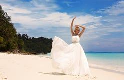 Mooie bruid in het elegante huwelijkskleding stellen op strand in Thailand Stock Fotografie