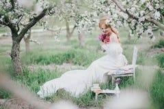 Mooie bruid in het uitstekende huwelijkskleding stellen in een bloeiende appeltuin Stock Afbeelding