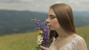 Mooie bruid in het verblijf van de huwelijkskleding op de bergen met boeket van bloemen stock videobeelden