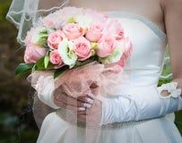 Mooie bruid in het witte boeket van de togaholding Stock Foto