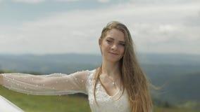 Mooie bruid in huwelijkskleding en sluier op de bergen Langzame Motie stock footage