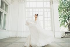 Mooie bruid in huwelijkskleding met lange volledige rok, witte achtergrond, dans en glimlach stock afbeelding