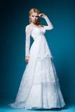 Mooie bruid in huwelijkskleding op blauw Stock Afbeelding