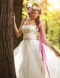 Mooie bruid met bloemtiara bij de boom Stock Fotografie