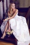 Mooie bruid met blond haar in elegante huwelijkskleding met boeket Stock Foto