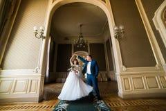 Mooie bruid met boeket en knappe bruidegom die blauw kostuum dragen die in boog bij gele murenachtergrond dansen stock foto