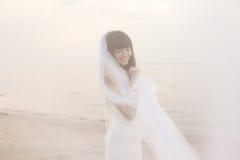 Mooie bruid met een lange sluier op het strand bij zonsondergang stock fotografie