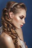 Mooie bruid met het kapsel van het manierhuwelijk - op blauwe achtergrond stock foto's