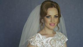 Mooie bruid met het kapsel van het manierhuwelijk - op witte achtergrond Close-upportret van jonge schitterende bruid Huwelijk stock videobeelden