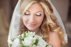 Mooie bruid met huwelijksboeket van bloemen makeup Blond c stock afbeelding