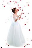 Mooie bruid op vloer onder rode roze bloemblaadjes Royalty-vrije Stock Foto