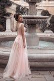 Mooie bruid in roze huwelijkskleding Openlucht romantisch portret van aantrekkelijke donkerbruine vrouw met kapsel in promkleding stock afbeelding