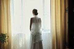 Mooie bruid in witte huwelijkskleding die zich in haar slaapkamer bevinden en in venster kijken stock foto's