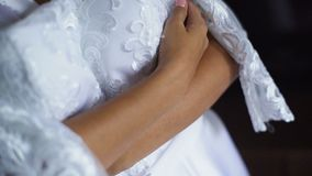 Mooie bruid in witte huwelijksnegligé holding en het koesteren van huwelijkskleding stock videobeelden