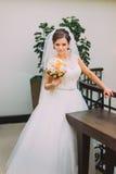 Mooie bruid in witte kleding die zich dichtbij het het huwelijksboeket van de balusterholding bevinden van bleek - roze rozen Stock Foto's