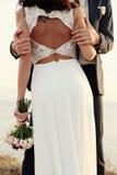 Mooie bruidegom en bruid in huwelijkskleren die op overzeese kust stellen Stock Afbeelding