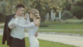 Mooie bruidegom met een jasje in zijn handen komst stock footage