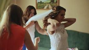 Mooie bruidsmeisjes die de gelukkige bruid helpen die gekleed worden stock footage