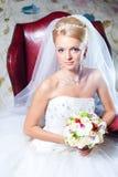 Mooie bruidzitting in rode leunstoel Stock Afbeeldingen