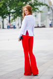 Mooie bruin-haired jonge vrouw die kleren en het lopen o dragen Stock Foto