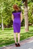 Mooie bruin-haired jonge vrouw die kleren en het lopen o dragen Stock Afbeelding