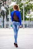 Mooie bruin-haired jonge vrouw die kleren en het lopen o dragen Royalty-vrije Stock Foto's