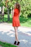 Mooie bruin-haired jonge vrouw die kleren en het lopen o dragen Stock Fotografie