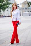 Mooie bruin-haired jonge vrouw die kleren en het lopen o dragen Stock Foto's