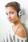 Mooie brunette die hoofdtelefoons draagt. Stock Afbeeldingen