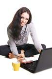 Mooie brunette met laptop die bij notitieboekje schrijft Royalty-vrije Stock Foto's
