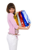 Mooie brunette met pakketten op handen Stock Afbeelding