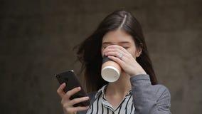 Mooie buisnesswoman het gebruiken smartphone en het drinken koffie, openlucht stock videobeelden