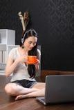 Mooie Chinese meisje het drinken thee die Internet gebruikt Stock Foto's