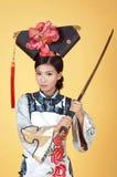 Mooie Chinese Vrouw die traditionele uitrusting dragen tegen gele achtergrond stock afbeelding