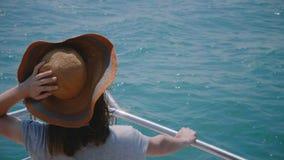 Mooie close-up achtermening van gelukkige opgewekte toeristenvrouw die in oude zonhoed van zonnig zeil op van de overzeese de voo stock videobeelden