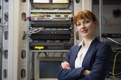 Mooie computertechnicus die bij camera glimlachen terwijl het bevestigen van server Stock Afbeeldingen