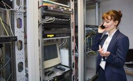 Mooie computertechnicus die op telefoon naast open server spreken Royalty-vrije Stock Fotografie