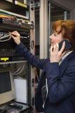 Mooie computertechnicus die op telefoon spreken terwijl het bevestigen van server Royalty-vrije Stock Fotografie