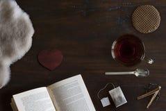 Mooie cozily vlak legt van kop thee, boek, schapehuid, koekje en kruiden stock foto