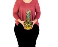 Mooie curvy meisjesholding en ananas stock afbeelding