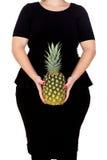 Mooie curvy meisjesholding en ananas royalty-vrije stock fotografie
