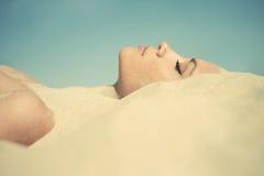 Mooie dame die in het zand wordt begraven Stock Foto