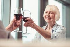 Mooie dame die rode wijn in een restaurant drinkt stock fotografie