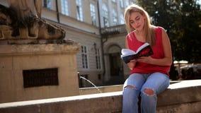 Mooie dame die terwijl het lezen van haar boek op het centrum van de stad glimlachen stock videobeelden